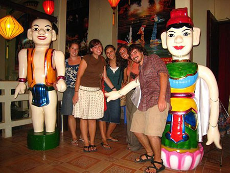 Tourists pose with water puppetry
